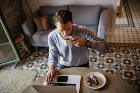 Handsome coworker man working at living room at home. Man sitting at wooden table using laptop and mobile phone. Blurred background Stock Photo - 105534747