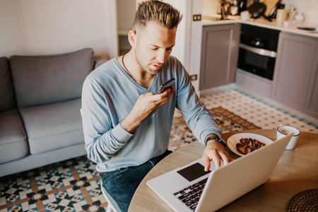 Working moments at home.Young caucasian coworker man in casual clothes working on laptop at modern apartment. Blurred background Stock Photo
