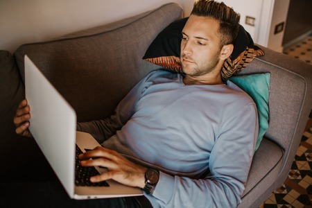 Working moments at home.Young caucasian coworker man in casual clothes working on laptop at sofa at modern apartment. Blurred background Stock Photo - 105534752