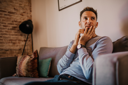Young handsome man wearing casual clothes relaxing on sofa at modern apartment Stock Photo