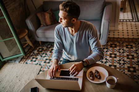 Handsome coworker man working at living room at home. Man sitting at wooden table using laptop and mobile phone. Blurred background Stock Photo - 105127599