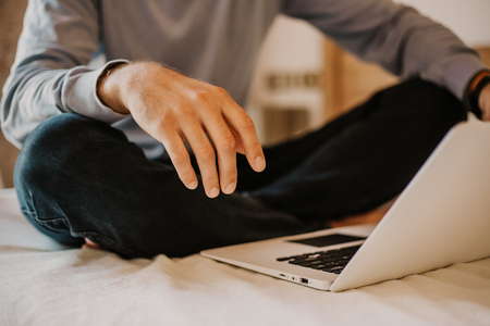 Working moments at home.Young caucasian coworker man in casual clothes working on laptop at modern apartment. Blurred background Stock Photo - 105255166