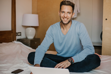 Working moments at home.Happy caucasian coworker man in casual clothes working on laptop at modern apartment. Blurred background Stock Photo - 105127603