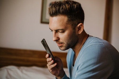 Handsome man using mobile smartphone for surfing web internet and sending audio message. Man using gadget at modern apartment Stock Photo - 105127604