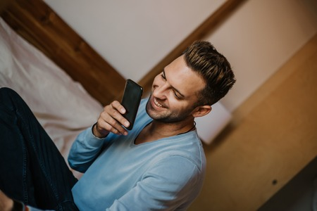 Handsome man using mobile smartphone for surfing web internet and sending audio message. Man using gadget at modern apartment Stock Photo - 105127605