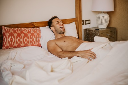 Shirtless sexy male model lying alone on his bed in his bedroom.Carefree guy enjoying new day Stock Photo - 105127544