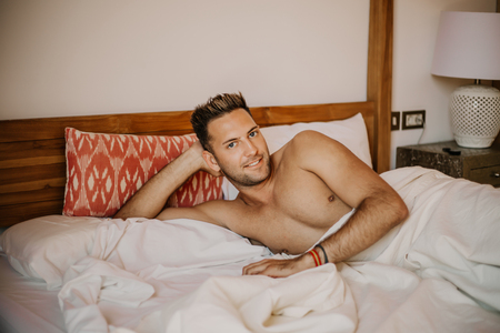 Shirtless sexy male model lying alone on his bed in his bedroom, looking at the camera with a seductive attitude.Carefree guy enjoying new day.