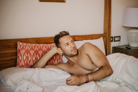 Shirtless sexy male model lying alone on his bed in his bedroom, looking away with a seductive attitude.Carefree guy enjoying new day. Stock Photo - 105127547