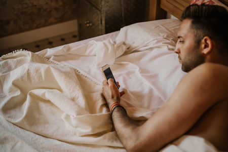 Carefree guy enjoying new day.Handsome young man in bed typing on cell phone, sending text message or dialing number. Stock Photo - 105127549