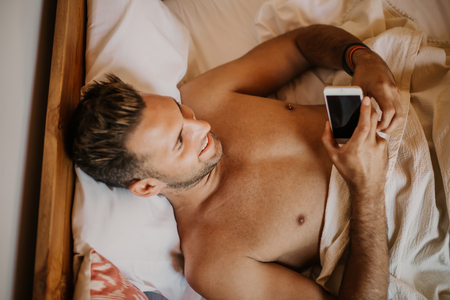 Carefree guy enjoying new day.Handsome young man in bed typing on cell phone, sending text message or dialing number. Stock Photo - 105127551