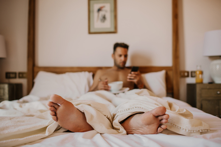 Handsome man lying on bed with smartphone, happy smile drink orange juce in the morning. Attractive guy smiling in bedroom at home, sexy young male model