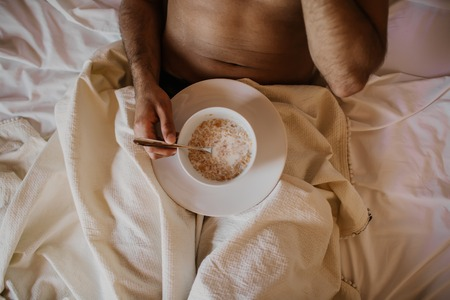 Handsome man lying on bed with healthy breakfast in the morning. Attractive guy smiling in bedroom at home, sexy young male model