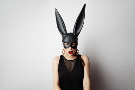 Sexy young woman with red lipstick and large breasts wearing a black mask. Easter bunny standing on a white background and looks very sensually.
