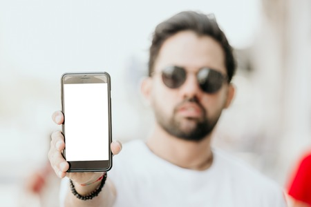 Young hispanic male holding hand cell phone with empty white copy space screen for your advertising content