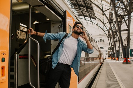 Confident Attractive young hispanic wearing sunglasses and blue shirt male holding smartphone hand and calling to friends while he standing at the train wagon on platform. 版權商用圖片