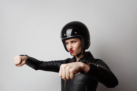 Portrait of young beautiful cheerful girl in black leather jacket pretending to ride a motorcycle isolated on white background