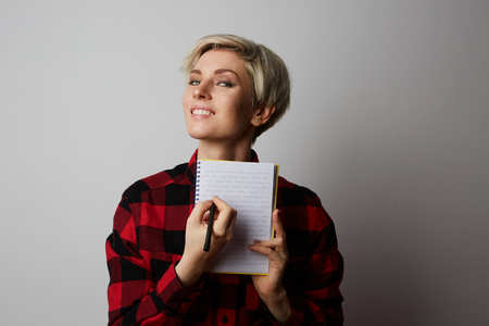Portrait of serious blonde girl posing in a red shirt in a big cage holding hand notepad and pen. Stock Photo