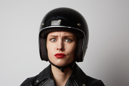 Headshot Portrait of girl with red lips in black leather jacket smiling looking at camera. White background. Fashion, glamour and emotions concept