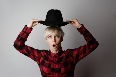 Headshot Portrait of happy blonde girl with black hat smiling looking at camera. White background. Fashion, glamour and emotions concept Stock Photo