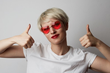Portrait Happy young blonde woman with short hair over empty white background.Girl showing ok sign and smiling.Positive human emotions, reaction, gestures and body language