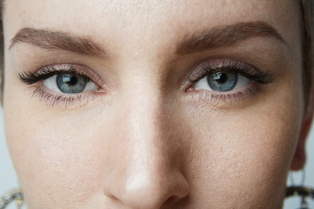 Close-up portrait Beauty women with big blue eyes and dark eyebrows looking at camera.Model with light nude make-up, gray studio background