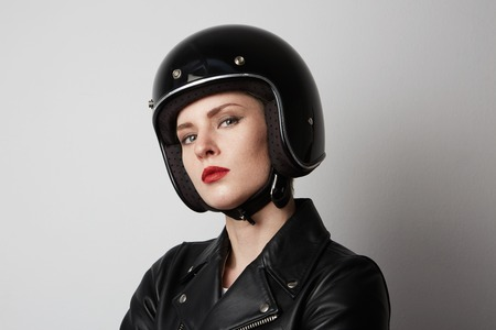 Headshot Portrait of fashion girl with red lips in black leather jacket smiling looking at camera over white background. Fashion, glamour and transportation concept