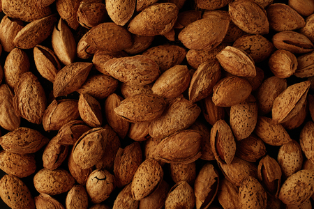 Top view of handful of pecans, almonds on a black background. Closeup. Micro