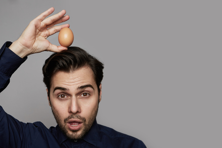 Attractive hispanic man holding chicken fresh organic egg over of head on gray background. Close up