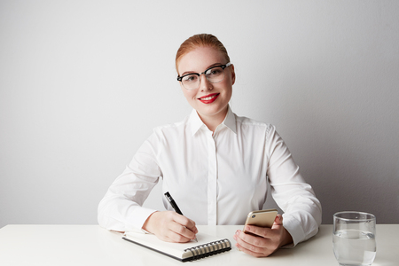 Beautiful redhead business woman working at the table over empty white background