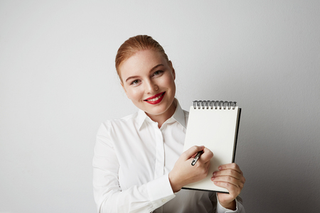 Portrait of trendy redhead woman posing in shirt holding empty notepad over white background