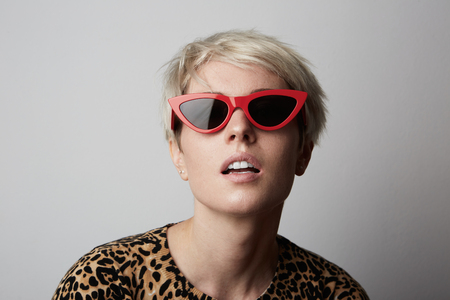 Fashion Portrait of young Fabulous trendy blonde woman with red sunglasses and white short hair poising at camera over white empty background Stock Photo