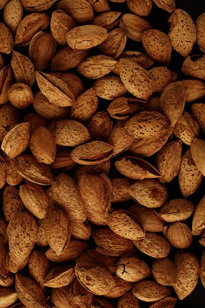 Top view of handful of pecans, almonds on a black background. Closeup. Micro. Vertical