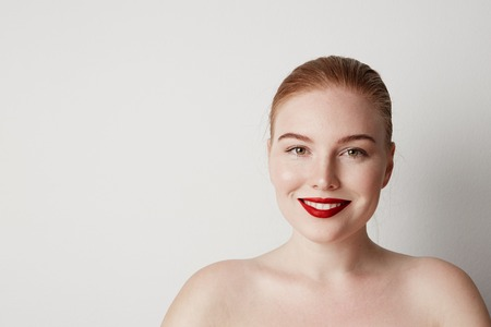 Handsome redhead female model with light nude make-up posing over white background