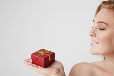 Beauty redhead woman holding hand red gift box over white empty background Stock Photo