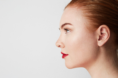 Profile portrait of beauty female redhead model with dark eyebrows and light nude make-up. Copy paste place 스톡 콘텐츠