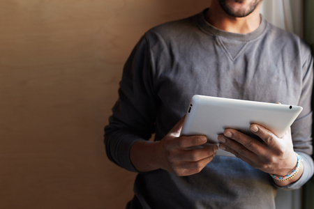 African american black man using electronic tablet at home.