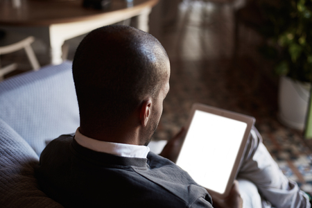 African black man using tablet on sofa couch in home living room Zdjęcie Seryjne