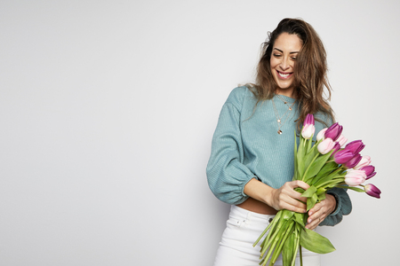 Portrait of a attractive young woman holding colored tulips bouquet isolated over gray background. Copy paste space. Stock Photo