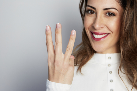 Handsome positive woman in white shirt looking at camera and showing hands gesture while standing isolated on gray background 写真素材