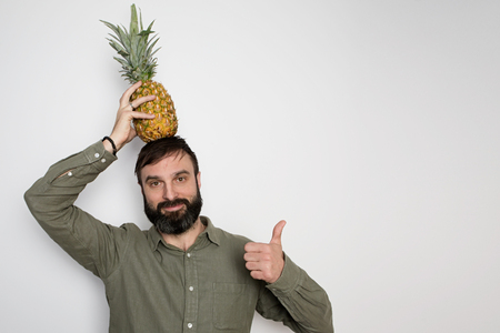 Bearded man and pineapple fruit tropical juice on background wall.