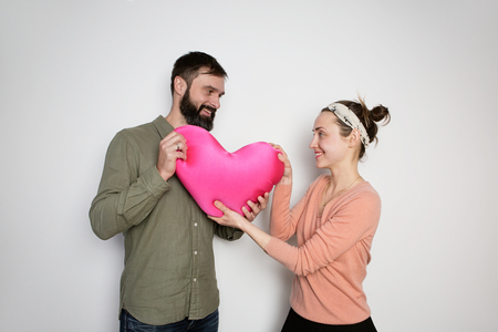 Bearded man gives red soft toy heart for his young girlfriend. Couple in love tears big heart on white background