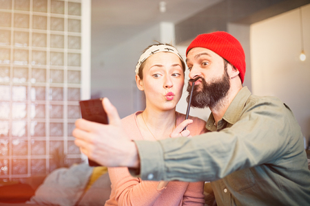 Cheerful young couple taking a humorous selfie with a smartphone. Romantic relationship between people