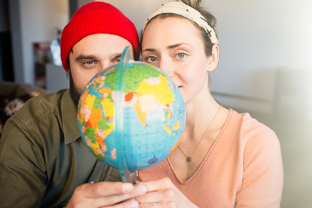 Portrait of Happy young couple with globe choosing place for summer journey. Family travel concept