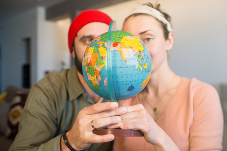 Portrait of Happy young family with worldwide globe choosing place for summer vacation. Family travel concept