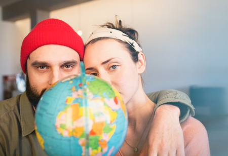 Happy young couple with globe choosing place for summer vacation at leisure. Family travel concept
