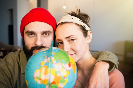 Happy young couple with globe choosing place for summer travel. Family travel concept