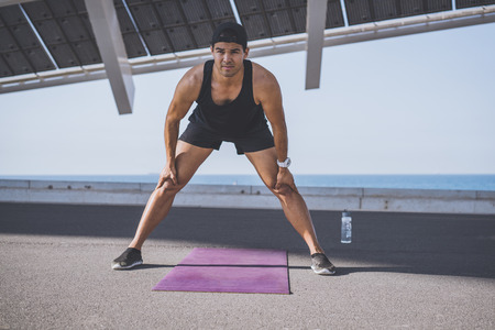Muscular Male athlete sprinter doing stretching exercise, exercising outdoors, jogging outside. healthy lifestyle Stock Photo