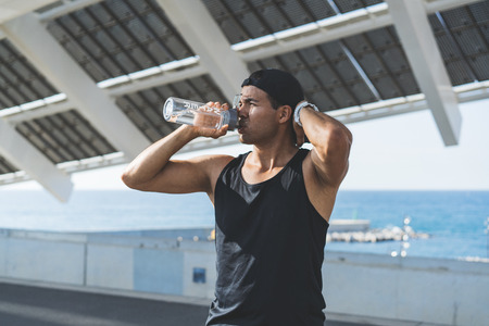 Muscular Male athlete sprinter drinking pure water after hard workout exercise. Healthy lifestyle
