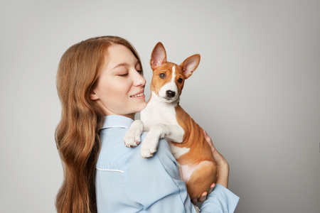 Beautiful red haired girl embracing puppy on white background. Studio portrait of white appealing woman chilling with dog. Stock Photo