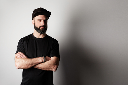 Bearded attractive man Wearing Black Tshirt Blank Snapback Cap on white background Stock Photo